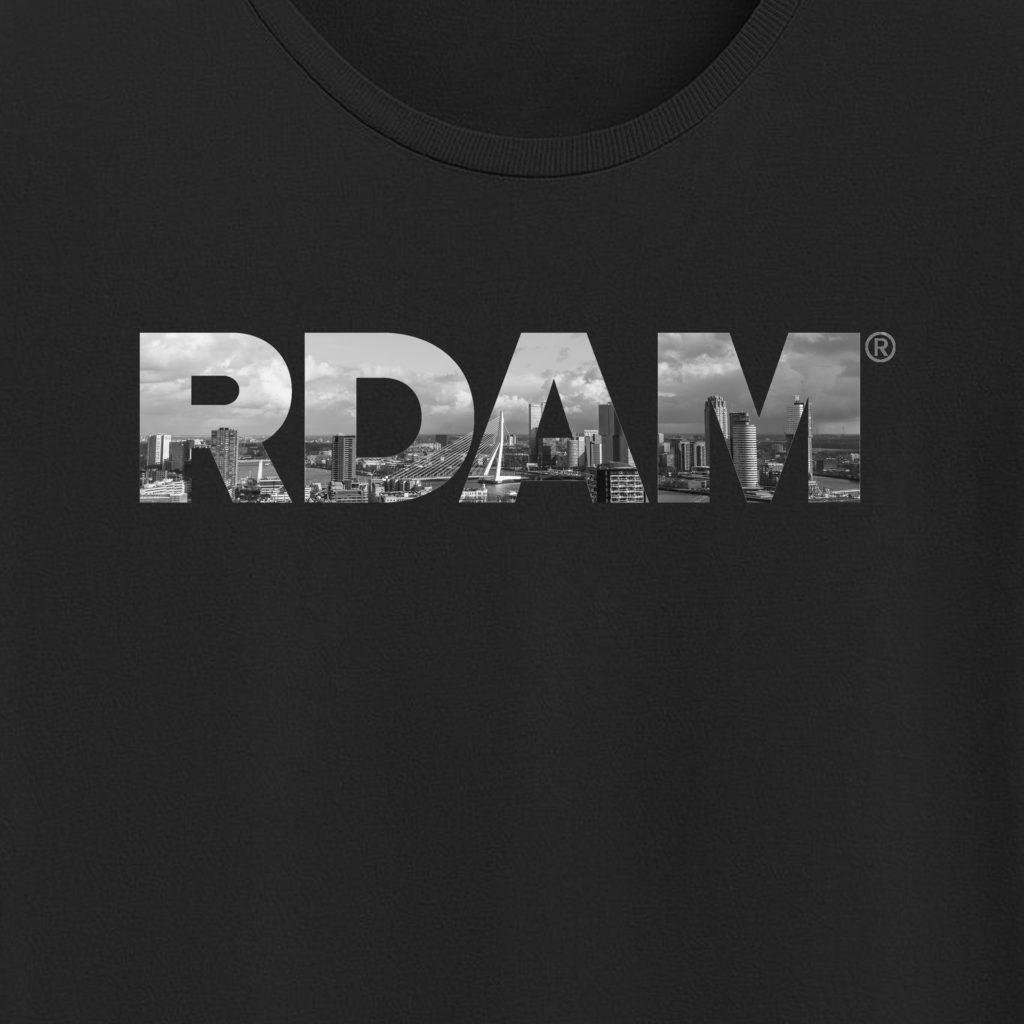 RDAM® t-shirt met de iconische letters en op de achtergrond de skyline van Rotterdam